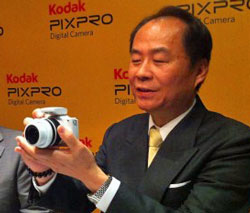Asia Optical founder and chairman Robert Lai launches Kodak Pixpro cameras this week on behalf of...who? According to Mr Lai, all R&amp;D and manufacture for Kodak cameras will be handled by Asia Optical, and help the company achieve sales growth of 30 percent in 2013, following a drop in revenue last year of 15 percent, attributed to Kodak's bankruptcy. He is showing the new Kodak mirrorless interchangeable S1, due for release in the third quarter. 