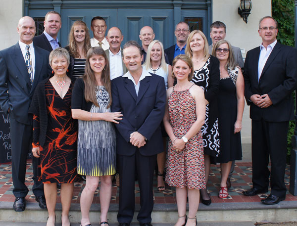 """The extended Photo Direct crew celebrate 10 years in business. Left to right: Mike, Brent, Tracy, Susan, Stephen, Jenny, Alan, Neil, Steven, Fiona, Stuart, Natalie, Christine, Steuart, Helen, Chris. The original 'Gang of 5' was Tracy Lints, Susan Smith,  Neil Glanville, Steuart Meers and Chris Howell. 'It wasn't a planned start-up so we didn't have many of the things you would normally have firmly in place before becoming an importer and distributor such as finance facilities, a warehouse facility, or even a freight company!' explained Tracy. 'As a result, it was all hands on deck – including those of husbands and wives- to do whatever was required whenever it was required. Home garages became warehouses overnight and private cars became couriers. We still do what is required when it's required, to make it happen, - and we still have the support of our """"other halves"""" so it was nice to be able to share the birthday celebrations with them by having a weekend away together.'"""