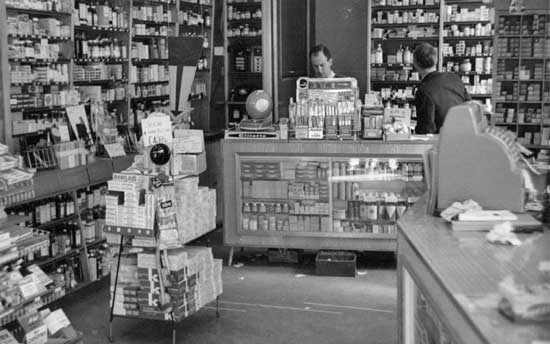 Michaels pharmacy interior in the 1950s with a young Alan Michael behind the counter.